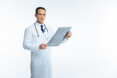 Serious medical worker with mri scan looking into camera. Ready to help. Mature doctor in a white coat standing straight and looking into the camera confidently stock images