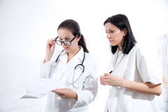 Serious medical workers looking at documentation. Studio shoot royalty free stock photography