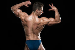 Serious Men Standing And Flexing Muscles Stock Photo