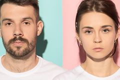 The serious man and woman looking at camera against pink and blue background. Serious men and women looking at camera isolated on trendy pink and blue studio Royalty Free Stock Image