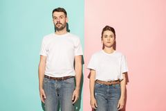 The serious man and woman looking at camera against pink and blue background. Serious men and women looking at camera isolated on trendy pink and blue studio Stock Photography