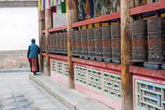 Woman Is Praying By Rotating Cylinders In Buddhist Temple stock photography