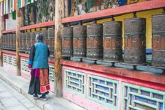 Woman Is Praying By Rotating Cylinders In Buddhist Temple royalty free stock image