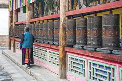 Woman Is Praying By Rotating Cylinders In Buddhist Temple royalty free stock photography