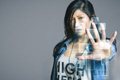 Serious mid adult woman touching futuristic computer screen over gray background Stock Images