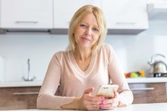 Serious middle age businesswoman using a smartphone royalty free stock image