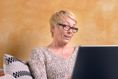 Serious Middle Age Woman on Sofa with Laptop Royalty Free Stock Image