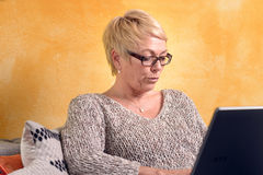 Serious Middle Age Woman on Sofa with Laptop Royalty Free Stock Photo