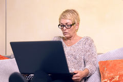 Serious Middle Age Woman on Sofa with Laptop Stock Image