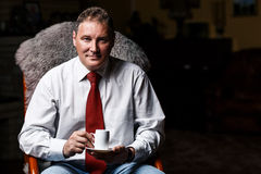 Serious middle-aged businessman with coffee cup stock photography