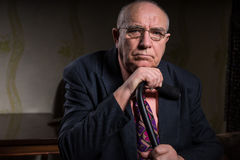 Serious Middle Aged Businessman Holding his Cane Stock Images
