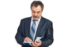 Serious middle aged corporate man writing Stock Image