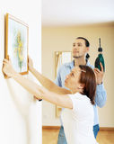 Serious middle-aged couple choosing place for picture in frame Stock Images