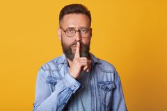 Serious middle aged emotionless bearded man in blue shirt, showing silence gesture, asks to keep secret, putting forefinger on. Lips, male dressed in denim royalty free stock image