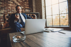 Serious middle aged male businessperson relaxing stock image