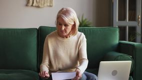Serious mature woman calculating bills holding documents using laptop. Serious middle aged mature woman calculating bills holding documents using laptop stock footage