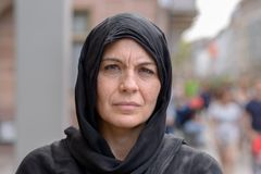 Serious middle aged woman wearing a head scarf. Serious middle aged woman wearing a black head scarf or hijab in a close up head shot in a busy urban street stock image