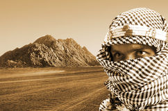 Serious middle eastern man. Portrait of serious middle eastern man in desert at sunset. Sepia toned Royalty Free Stock Images