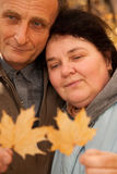 Serious middleaged man and woman hold maple leaves Stock Photography