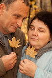 Serious middleaged man and woman hold maple leaves Royalty Free Stock Image
