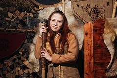 Viking sword handles sword rack reenactment forge smith warrior weapon outfit ax shield skin hearth one woman girl portraite Royalty Free Stock Photography