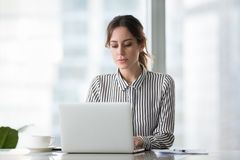 Serious businesswoman working online using laptop at office royalty free stock image