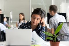 Serious millennial indian woman employee talking on phone in off. Serious millennial indian women employee talking on the phone making call at work, young hindu royalty free stock photo
