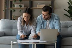 Free Serious Millennial Spouses Calculate Expenses Sit On Sofa At Home Stock Photography - 225337362