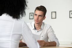 Serious male employee listening to colleague arguments on financ Stock Photography
