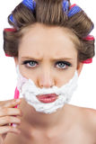 Serious model in hair curlers posing with shaving foam and razor. On white background Stock Images
