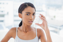 Serious model using her asthma atomizer Stock Image