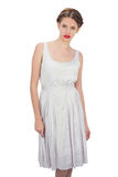 Serious model in white dress posing looking at camera Royalty Free Stock Images