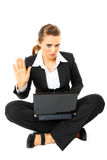 Serious modern business woman showing stop gesture. Sitting on floor with  laptop serious modern business woman showing stop gesture  isolated on white Stock Photography