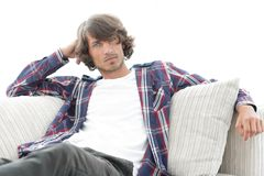Serious modern guy sitting on the couch. Photo with blank space for text Royalty Free Stock Image