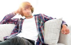 Serious modern guy sitting on the couch. Photo with blank space for text Royalty Free Stock Photography