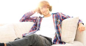 Serious modern guy sitting on the couch. Photo with blank space for text Stock Photography