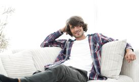 Serious modern guy sitting on the couch. Photo with blank space for text Stock Image