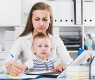 Serious mom with child is сoncentratedly working behind laptop royalty free stock photos
