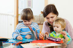 Serious mother and children sketching with pencils Stock Photos