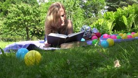 Serious mother student study book on plaid and newborn baby crawl. 4K stock video footage