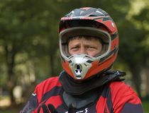 Serious motocross rider geared up. Caucasian male motorcross rider with full gear on including helmet and neck brace stock photo