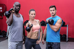 Serious muscular athletes lifting kettlebells. Portrait of serious muscular athletes lifting kettlebells Stock Images