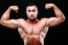 Serious muscular man showing his biceps Royalty Free Stock Photo