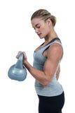 Serious muscular woman lifting kettlebell Stock Photos