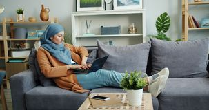 Serious Muslim woman in hijab working with laptop sitting on sofa at home. Typing looking at screen. Modern technology, lifestyle and house activity concept stock video footage