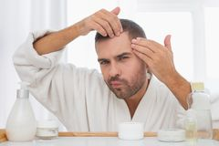 Serious nice man looking at his face. Skin imperfections. Serious nice man looking at his face while searching for skin imperfections royalty free stock image