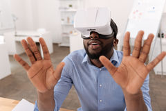 Serious nice man pressing his hands to the virtual screen Stock Images