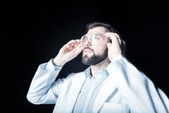 Serious nice scientist putting on safety glasses. Laboratory outfit. Serious handsome nice scientist standing and looking in front of him while putting on safety Royalty Free Stock Photos