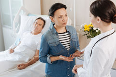 Serious nice woman asking about her husbands condition. How serious is it. Pleasant nice serious women looking at the doctor and asking about her husbands Royalty Free Stock Photography