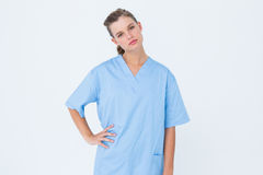 Serious nurse in blue scrubs posing with hand on hip Royalty Free Stock Images